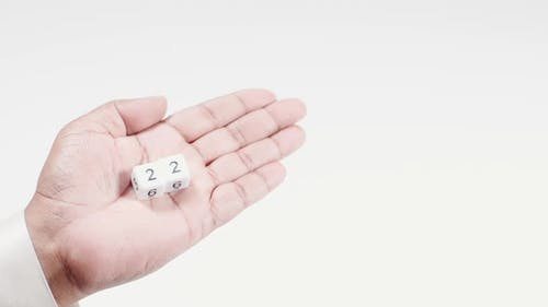 Hand hält nummerierte Würfel Zwei und Zwei Zwei Zwanzig