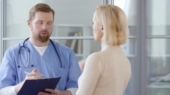 Cover Image for Young Male Doctor Writing on Clipboard and Talking with Woman