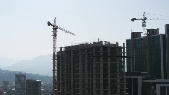 Thumbnail for Tower Crane on a Construction Site Lifts a Load at High-rise Building. Timelapse.