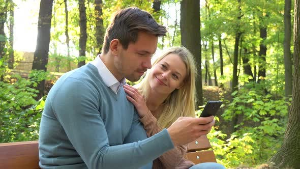 Thumbnail for A Young Attractive Couple Looks at a Smartphone on a Bench in a Park on a Sunny Day, Closeup