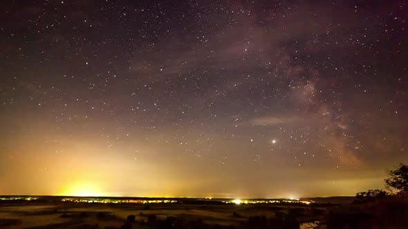Starry Night in Mountains Time Lapse. Milky Way Galaxy Stars Moving Over Countryside Traffic. Night