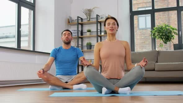 Couple Meditating in Yoga Lotus Pose at Home