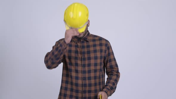 Cover Image for Happy Young Bearded Indian Man Construction Worker Giving Hardhat