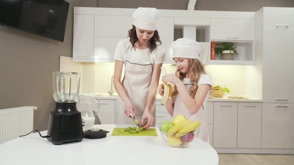 Thumbnail for Attractive Woman and Little Girl Cutting Fruits for Cocktail