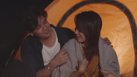 Young asia couple backpackers enjoying in camping at night near campfire on beach.