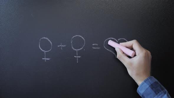 Drawing feminine symbols with pink chalk on chalkboard. Feminism concept
