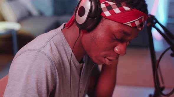 Thumbnail for Afro-American Man Writing Lyrics to Hip-Hop Music in Home Recording Studio