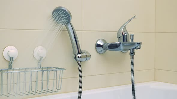 Cover Image for Closeup on a Luxurious Bathtub with the Shower Head on