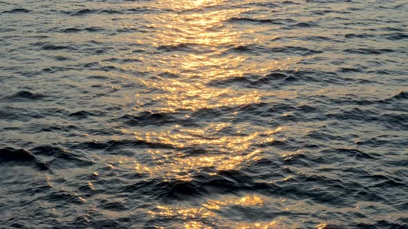 Cover Image for Background of Calm Sea. Sea with Little Waves Close Up. Deep Blue Ocean with Sun Reflecting in the