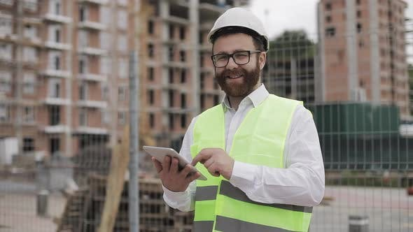 Thumbnail for Portrait of a Successful Young Businessman, Wearing a White Helmet, in a Suit Working with Tablet