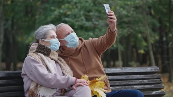 Adult Couple in Medical Masks, Sits on a Bench in a Forest Park and Take a Selfie Video on a