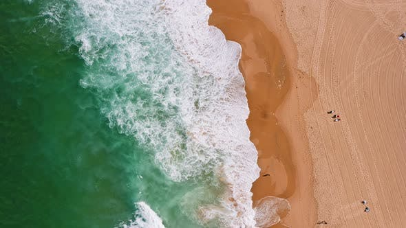 Top Aerial View of Waves Break on Tropical Yellow Sand Beach. Bird's Eye Perspective of Emerald