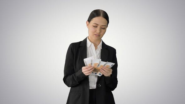 Thumbnail for Brunette woman counting euro banknotes and looking to camera