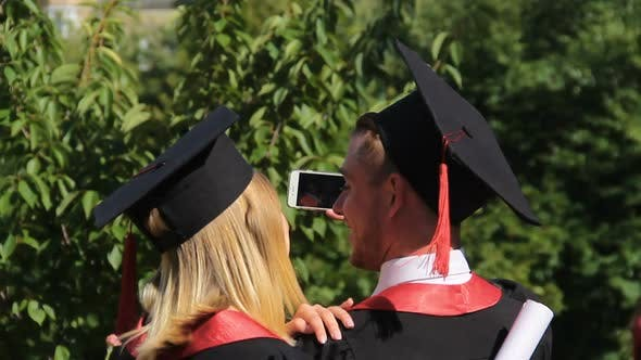 Cover Image for Couple of Joyful Graduates Recording Video on Smartphone, Graduation Ceremony
