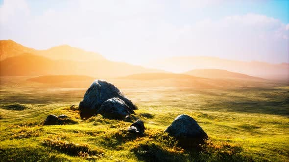 Meadow with Huge Stones Among the Grass on the Hillside at Sunset