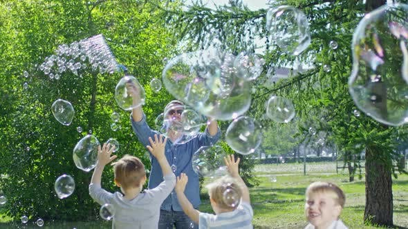 Thumbnail for Performer Blowing Bubbles for Playful Kids in Park