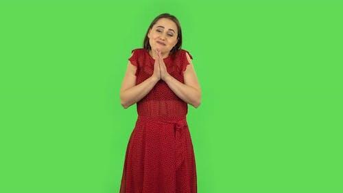 Tender Mädchen in rotem Kleid hält Palm zusammen und fragt nach etwas. Grüner Bildschirm