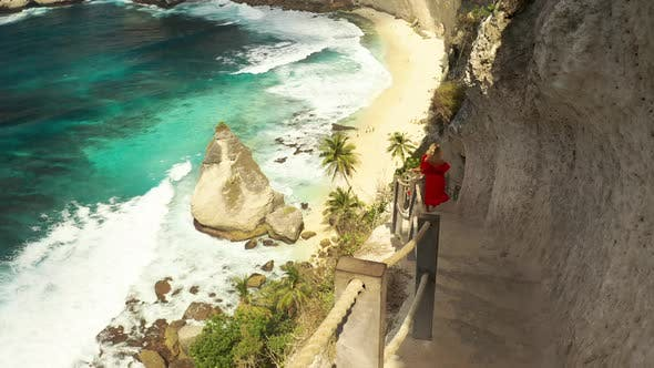 Thumbnail for A Young Blonde Woman Descends To a Tropical Beach on the Stairs Cut Down in a Rock at the Diamond