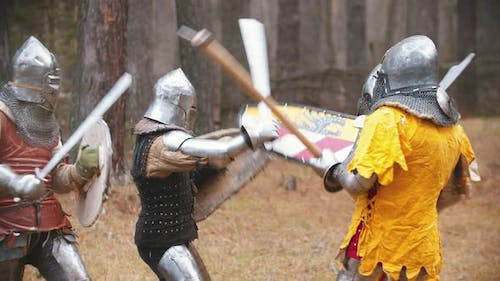 Four Men Knightes Having a Training Fight on the Field in the Middle of the Forest