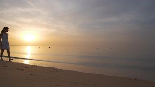 Young woman walking alone on sandy beach by seaside enjoying warm tropical evening.