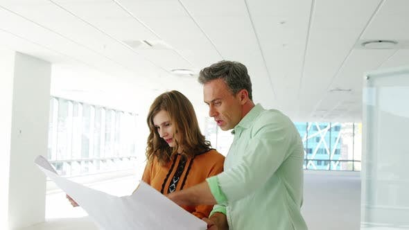 Thumbnail for Business people discussing over blueprint in a modern office