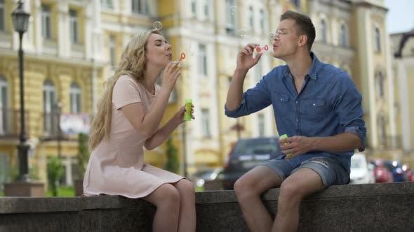 Cover Image for Junges Paar machen Seifenblasen, Erreichen einander zu küssen, Verspieltheit