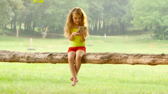 Thumbnail for Cute Little Girl Playing on Smartphone Sitting on a Tree