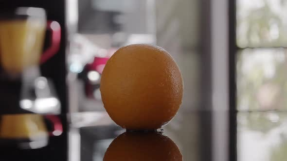Cover Image for A Closeup of a Wet Orange Spinning on a Glossy Surface
