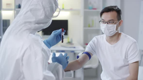 Thumbnail for Doctor in Protective Gear Discussing Blood Sample with Patient