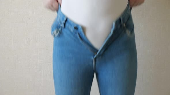 Young Woman Struggles To Button Her Jeans