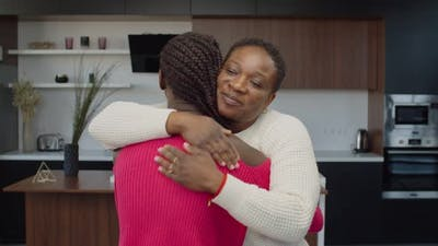 Caring Black Mother Embracing Teenage Daughter Indoor