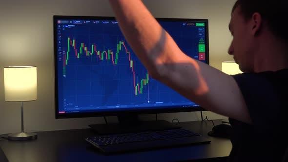 Thumbnail for Ein Mann sitzt an einem Tisch, sieht auf einem Kerzendiagramm auf einem Computerbildschirm und tanzt
