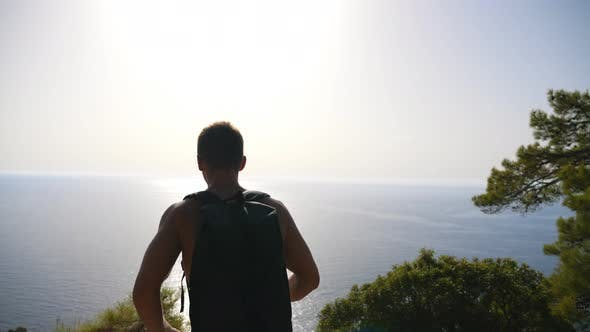 Thumbnail for Hiker with Backpack Reaching Up Edge of Mountain and Raising His Hands Admiring Scenic Seascape. Man