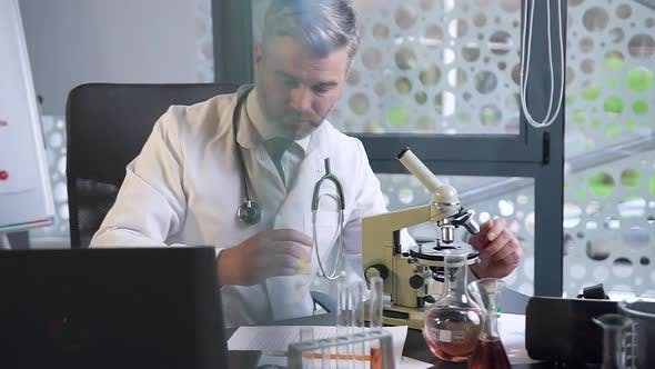 Thumbnail for Male Doctor Which Working in the Clinic Lab, Looking Into Microscope and Typing the Datas