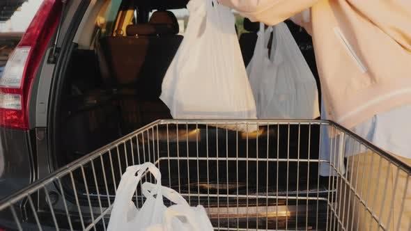 Thumbnail for Eine Frau entlädt Einkaufstaschen aus einem Korb im Kofferraum eines Autos