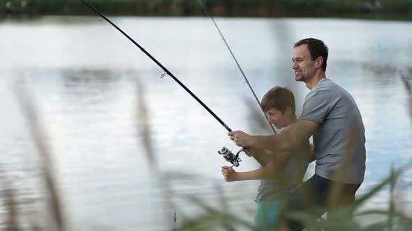 Thumbnail for Excited Father and Son Pulling Fish Out From Lake