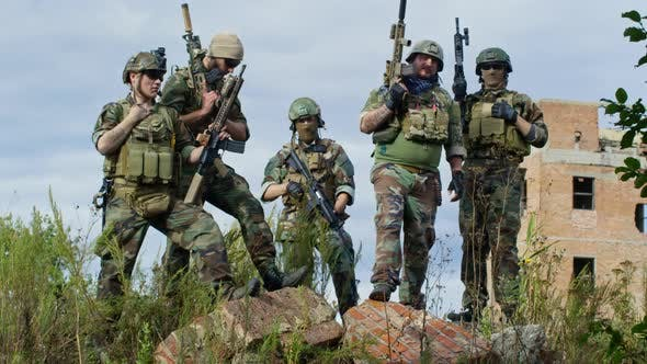 Thumbnail for Military Men Posing with Weapons Outdoors