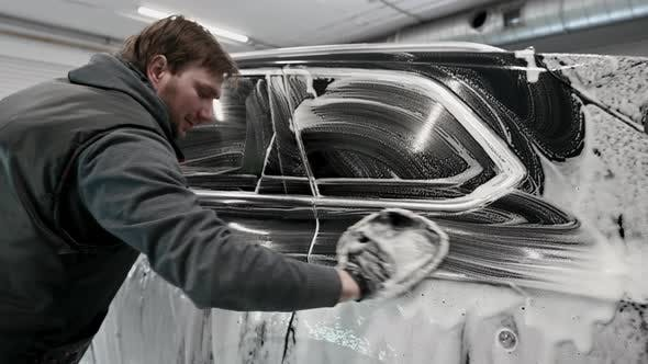 A Man Making Manual Car Wash on a Black Car with Special Cleaning Glove