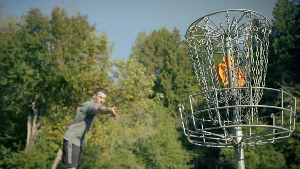Thumbnail for Man Practicing Frisbee Golf Throws Disc In Basket