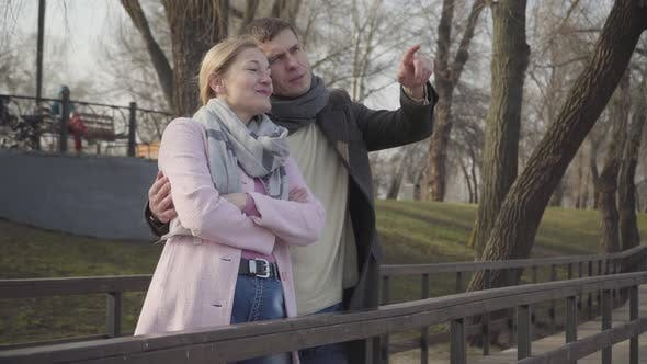 Thumbnail for Portrait of Young Caucasian Man in Love Pointing Away and Talking To Older Woman. Happy Couple