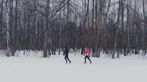 Thumbnail for Man and Woman in the Winter Running Through the Park in Slow Motion