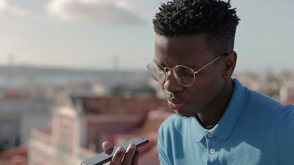 Thumbnail for Junge Afroamerikaner Mann mit ernsthaften Gesprächen auf Smartphone.