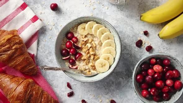 Thumbnail for Ceramic Bowl of Oatmeal Porridge with Banana, Fresh Cranberries and Walnuts