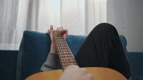 Young Woman Hand Playing Chords on Guitar