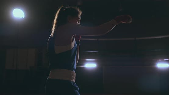 Cover Image for Steadicam Shot Professional Beautiful Female Boxer Unloads Strikes While Conducting a Shadow Fight