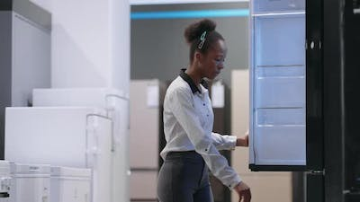 Afroamerican Housewife is Choosing Fridge in Home Appliance Store Viewing Exhibition Sample Inside