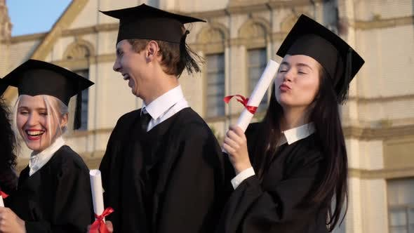 Thumbnail for Graduating Students Smiling and Laughing with Diplomas.