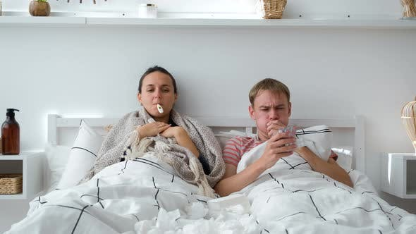 Couple Lying in Bed with High Fever and Flu