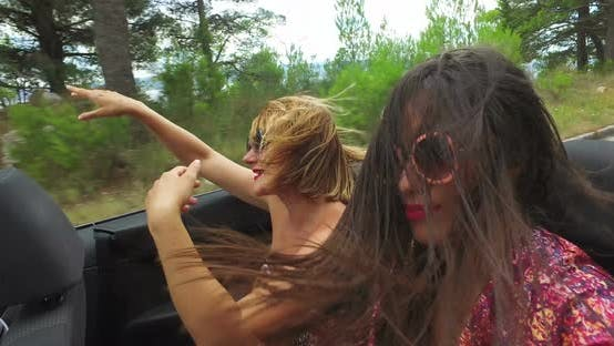 Thumbnail for Two carefree girls partying while riding in cabriolet