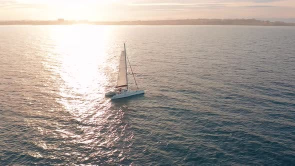 Aerial View. Catamaran Goes By Sea, Camera Move Closer and Fly Over Vessel, on the Sunset